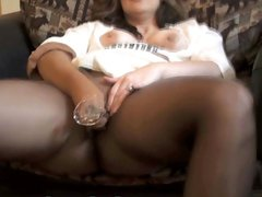 Brunette MILF sits on her chair in nylons and rubs her pussy