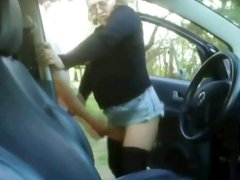 Dude is jerking his cock in the car and brunette walks by then helps